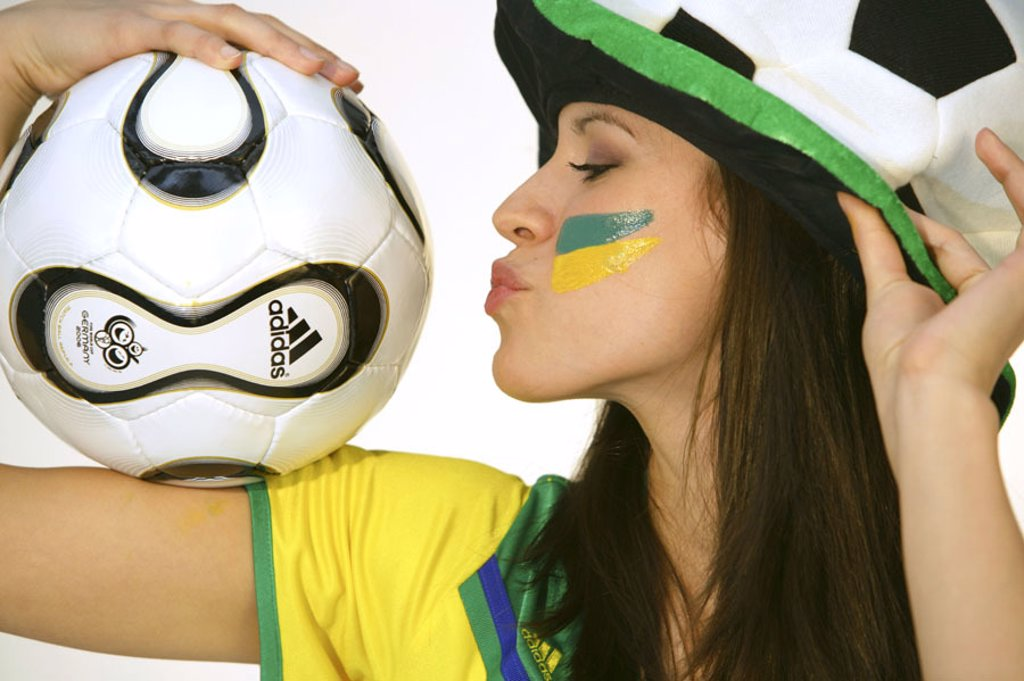 Stock Photo: 1558-98956 Woman, young, football fan, fan articles,  Ball, holding, kiss, profile,  no property release,  Series, 20-30 years, long-haired, brunette, nicely, radiation, youth, cheerfully, fun, enthusiasm, top, yellow, fan, hat, headgear, football hat, cleverly, foo