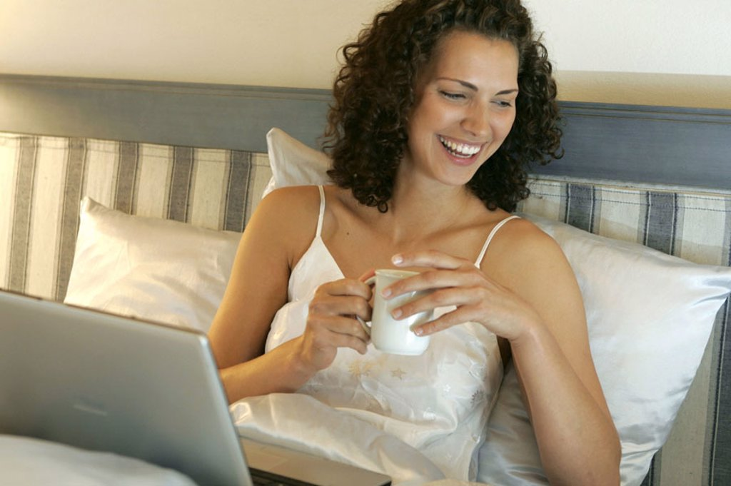 Stock Photo: 1558-99056 Bed, woman, young, smiling, Kaffeetasse,  wegstellen, laptop,   Series, 20-30 years, long-haired, curls, curly, brunette, leisure time, relaxen, mobility, enjoy flexibility, computers wearable internet internet access online, User, chatten, e-mail, happin