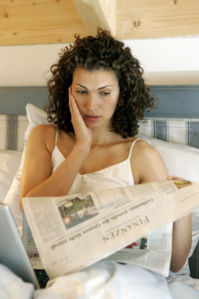 Stock Photo: 1558-99058 Bed, woman, young, horrifies, newspaper reading,  Laptop, portrait,   Series, 20-30 years, long-haired, curls, curly, brunette, nicely, leisure time, mobility, flexibility, computers, wearable, internet, internet access, online, User, chatten, e-mail, new