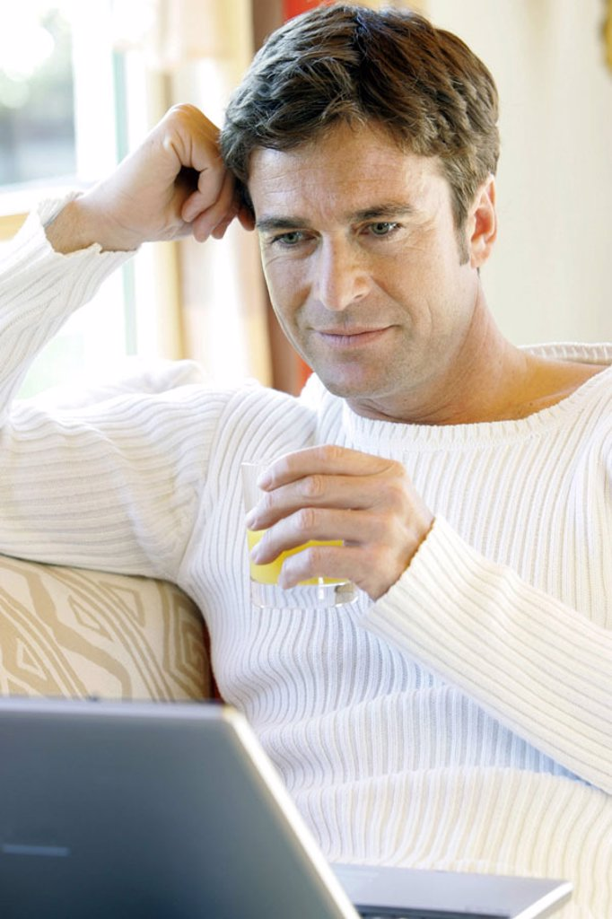 Stock Photo: 1558-99138 Living rooms, sofa, man, sitting,  Laptop, juice glass, portrait,   Series, 30-40 years, dark-haired, leisure time, Lifestyle, recuperation, relaxation, head, relaxen, resting e-mail computer communication telecommunication, internet, internet access, Int