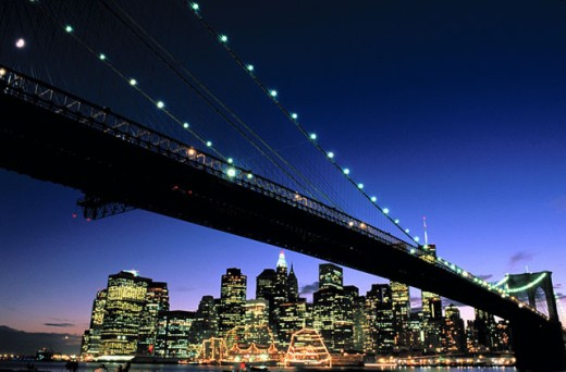Stock Photo: 1566-0102488 Twilight view of the financial district of lower Manhattan from Brooklyn with a silhouette of the Brooklyn Bridge and the East River in the foreground