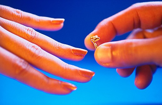 Man slipping ring on ladies finger : Stock Photo