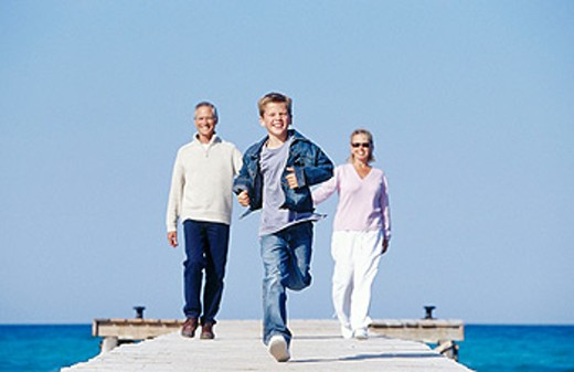 Stock Photo: 1566-0111323 Father, mother and child walking in a wooden footbridge over the sea