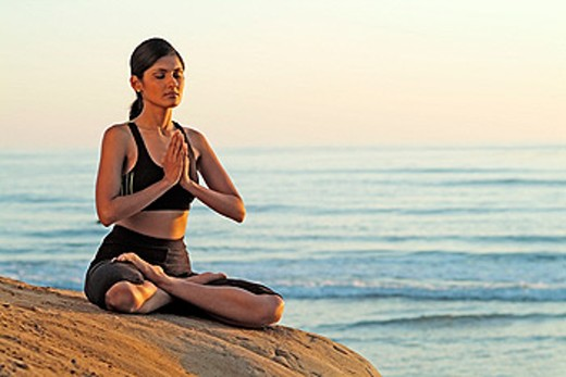 Indian girl meditating on beach in Carlsbad. California, USA : Stock Photo