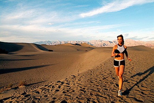 Stock Photo: 1566-0118043 Young woman running sand dunes in Death Valley, California. USA