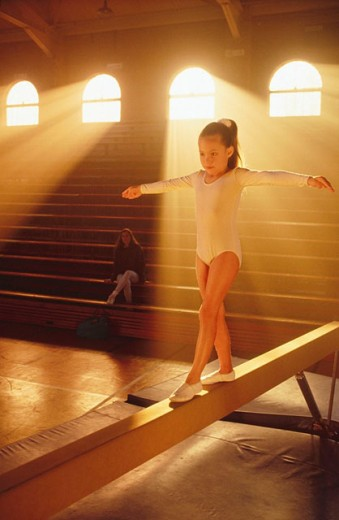 Young girl practicing on balance beam. : Stock Photo