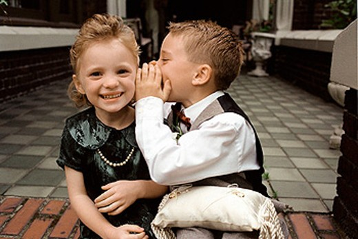Children whisper to each other as they prepare to be ring bearers at a wedding : Stock Photo