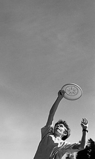 Boy catching frisbee : Stock Photo
