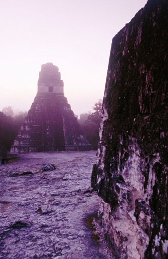 Stock Photo: 1566-0139124 Silhouette of the Temple of the Giant Jaguar at sunrise. Gran Plaza. Mayan ruins of Tikal. Peten region. Guatemala