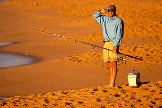 Stock Photo: 1566-0142273 Surfcasting at Playa Solmar in early evening, beach, man hold fishing rod, tackle box on sand. Cabo San Lucas. Mexico