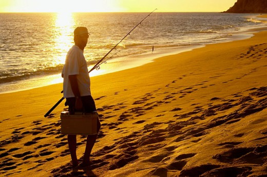 Stock Photo: 1566-0142290 Man surfcast at Playa Solmar, walk with tackle box and pole on sandy beach, barefoot. Cabo San Lucas. Mexico