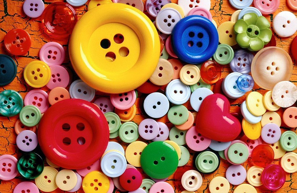 Stock Photo: 1566-0145503 A pile of buttons with a relly big yellow one