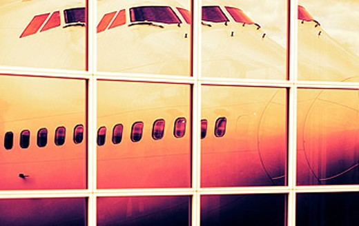 Boeing 747 aircraft reflected in airport terminal windows : Stock Photo