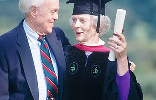 Senior woman wearing graduation cap and gown being congratulated by her husband on receiving degree : Stock Photo