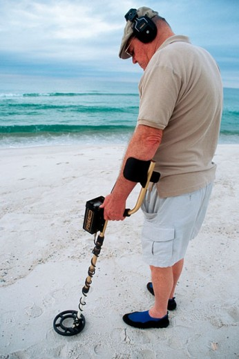 Stock Photo: 1566-0157947 Man using metal detector. Panama City beach, Florida. USA