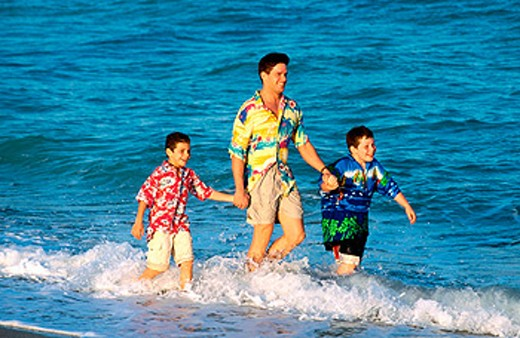 Boys walking through the waves with dad : Stock Photo