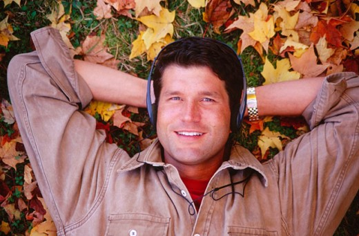 Stock Photo: 1566-0159003 Listening to music on leafy lawn