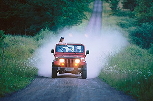Stock Photo: 1566-0159024 teens traveling country road in jeep