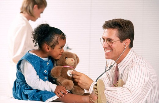 Pediatric doctor, patient, and teddy bear : Stock Photo
