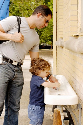 Stock Photo: 1566-0168999 Father helping his child drink some water from a fountain