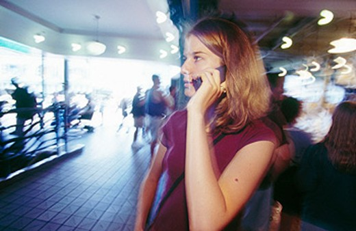 Stock Photo: 1566-0172255 Girl on cell phone, Pike Place Market, Seattle.