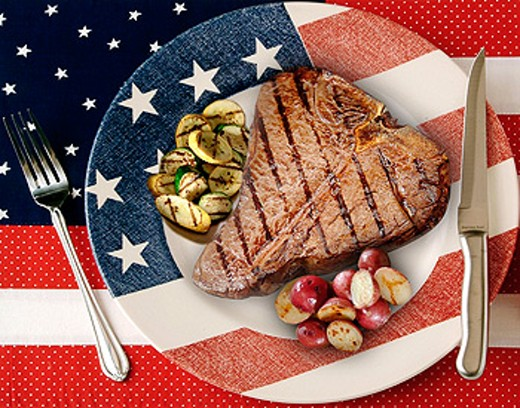 Tbone steak decked out in American flag dish, red potatos and zucchini sides : Stock Photo