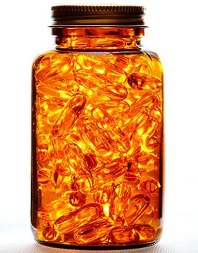 Vitamine E capsules in jar on white background. : Stock Photo