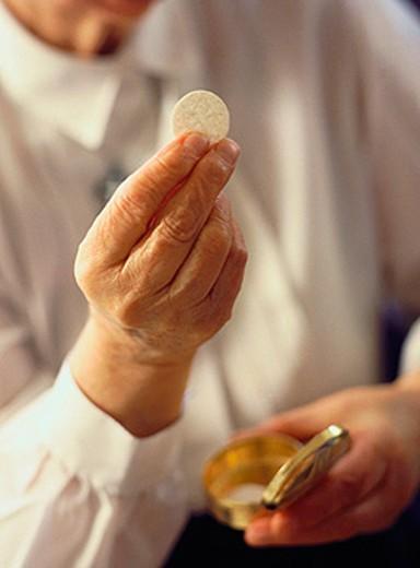 Stock Photo: 1566-017740 Giving communion