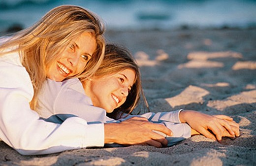 mother and daughter lying on the sand : Stock Photo