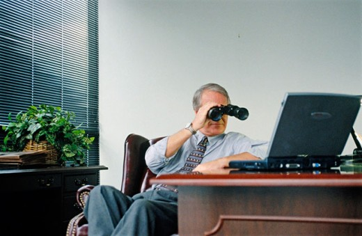Stock Photo: 1566-0177760 businessman looking at lap top with binoculars
