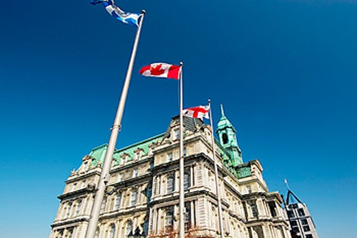 Stock Photo: 1566-0178233 The Quebec, Canadian and Montreal City flags outside the Montreal City Hall (Hotel de Ville) near Place Jacques Cartier in Old Montreal (Vieux Montreal). Quebec, Canada