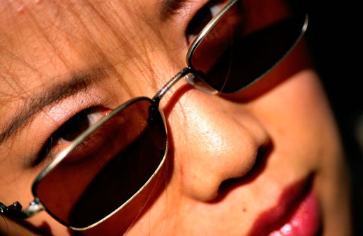 Portrait of a young Chinese woman, eyes looking over sun glasses at camera : Stock Photo