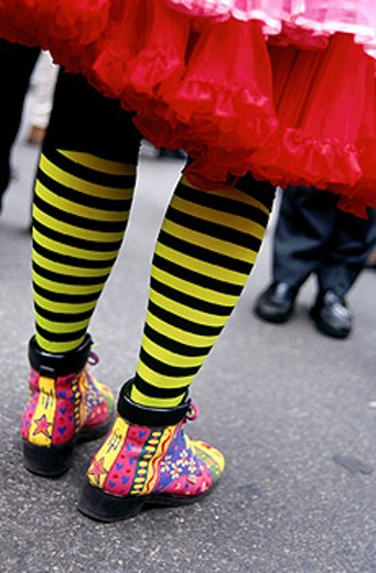 back side and partial leg view of colorful stockings and shoes of a clown : Stock Photo