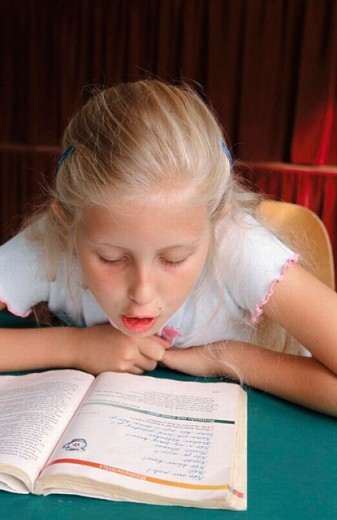 Young girl reading from text book at school : Stock Photo