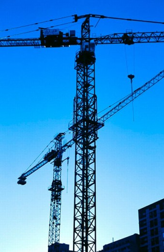 Silhouetted commercial work cranes : Stock Photo