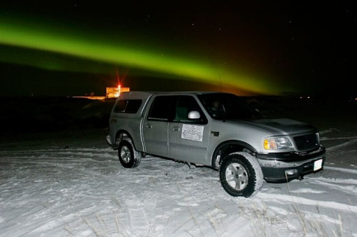 Stock Photo: 1566-0205129 Aurora Borealis (northern Lights) over truck and the snow covered shore of Hudson Bay, Churchill, Manitoba, Canada.