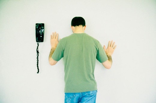 Stock Photo: 1566-020535 Unhappy young man next to phone