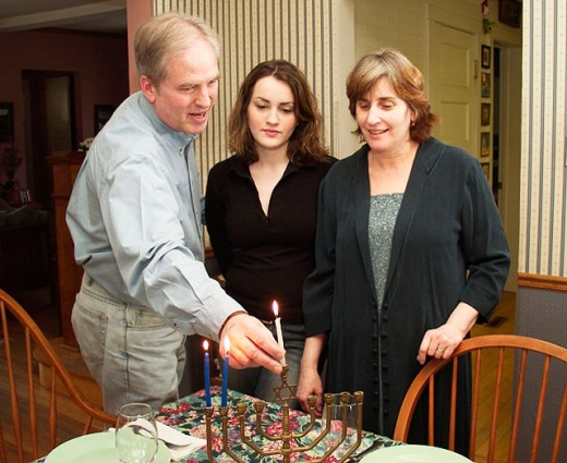 Parents and daughter lighting menorah at Hannukah : Stock Photo