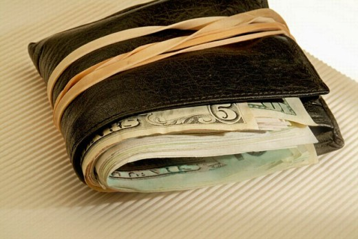 Wallet full with USA currency closed with rubber bands. : Stock Photo