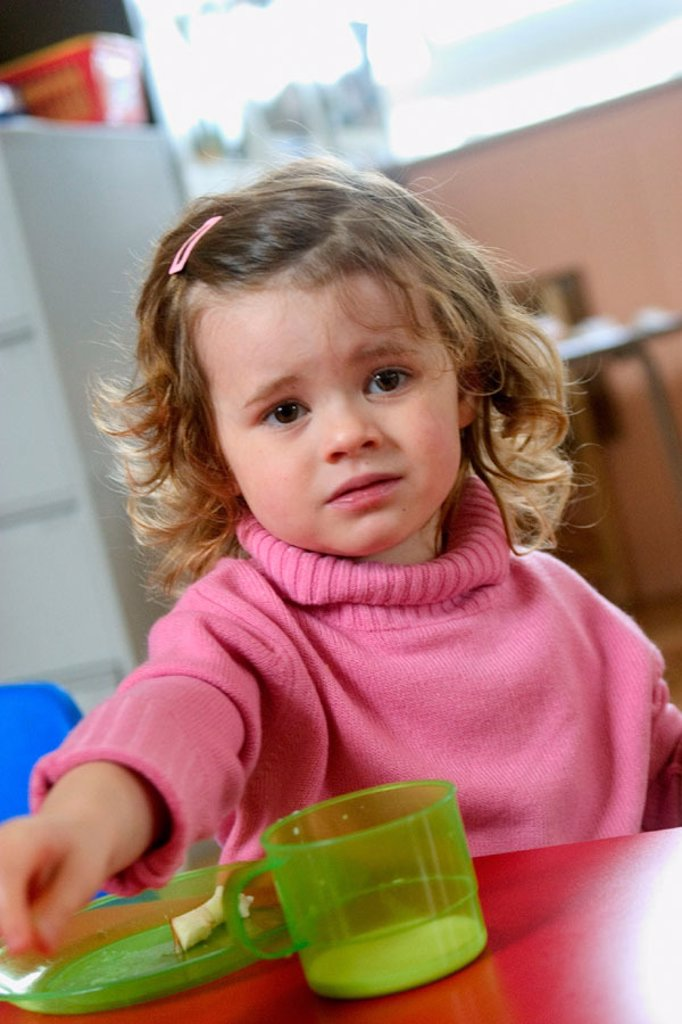 Stock Photo: 1566-0214693 Three year old girl with a plate and cup, looking miserable
