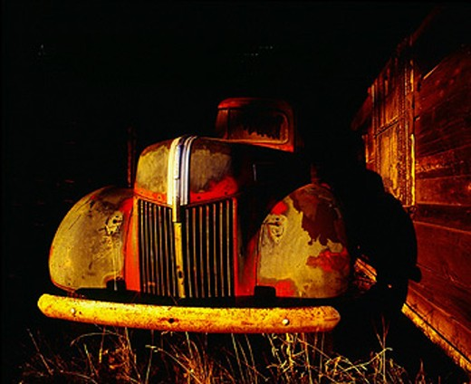 Stock Photo: 1566-0215457 Old truck in a barn with warm sun on it.