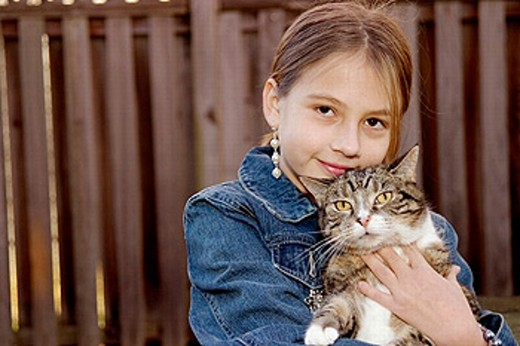 Stock Photo: 1566-0217203 10-year-old girl and her cat standing in her backyard in Annapolis, Maryland
