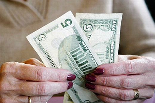Female hands holding two 5 dollar bills, one new and one old : Stock Photo