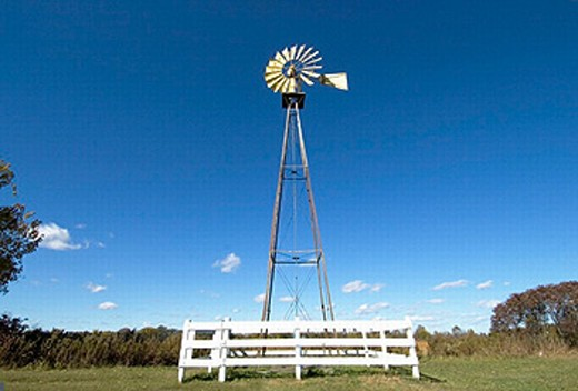 Windmill provides water drawing power on a rural farm : Stock Photo