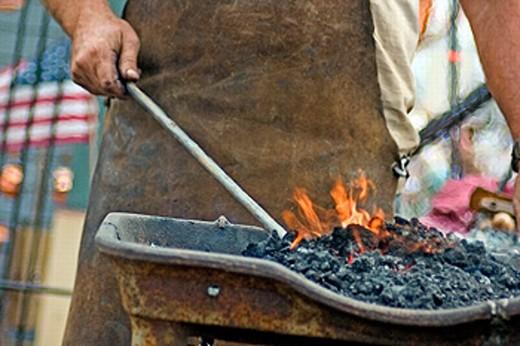 Stock Photo: 1566-0222824 Blacksmith working in hot coals. Bridgeton, Indiana, Covered Bridge Festival. USA.