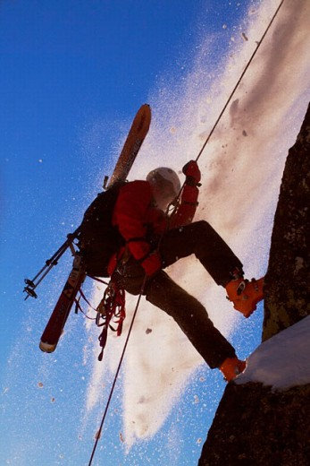 Stock Photo: 1566-0223846 Man rappelling during small avalanche with skis on his back on Donner Summit, California. USA
