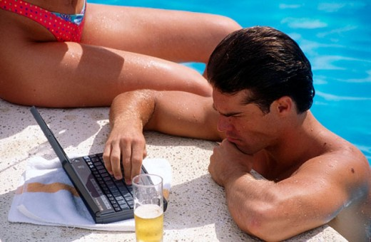Stock Photo: 1566-023749 Man working with laptop computer in the pool
