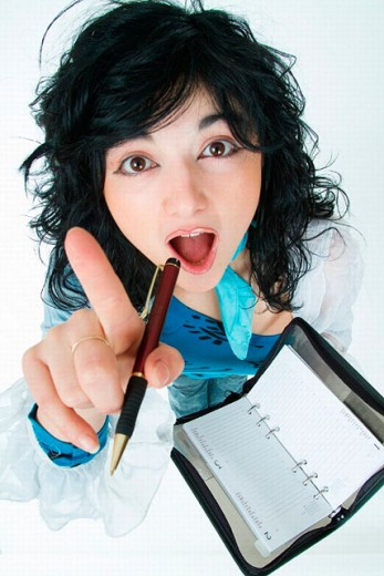 Surprise brunette taking pen in hand indicates with her finger towards the camera in the other hand has a calendar with appointments : Stock Photo