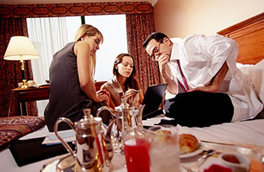 Businesspeople working on bed in hotel room : Stock Photo