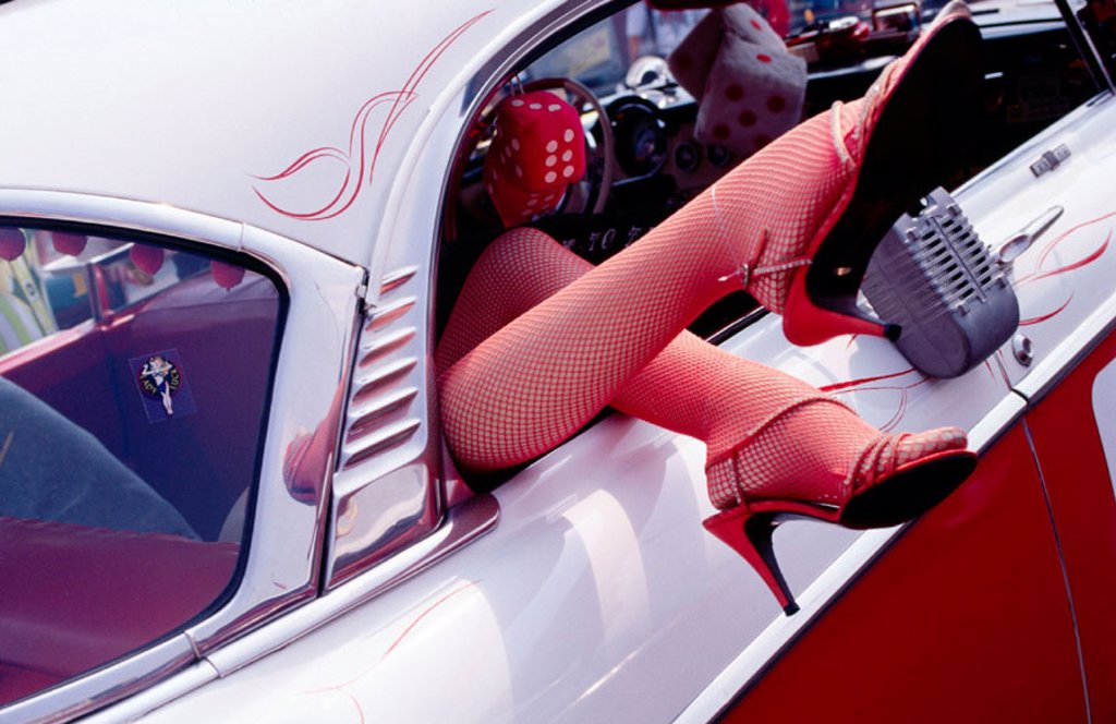 Stock Photo: 1566-032563 Woman´s legs wearing high heel shoes and stockings sticking out of the rear window of a 1950´s car